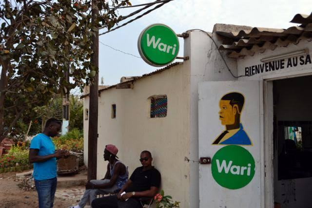 Men talk outside a hair salon that also offers money transfers through Wari in Dakar, Senegal March 15, 2017.