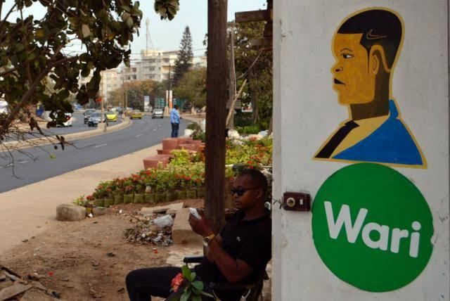 A man uses his mobile phone while sitting outside a hair salon that also offers money transfers through Wari in Dakar, Senegal March 15, 2017.